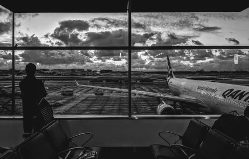 Sole traveller watching Qantas plane at empty airport
